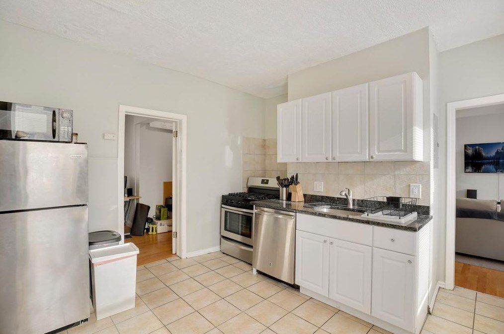 A spacious kitchen with a single counter and cabinets.
