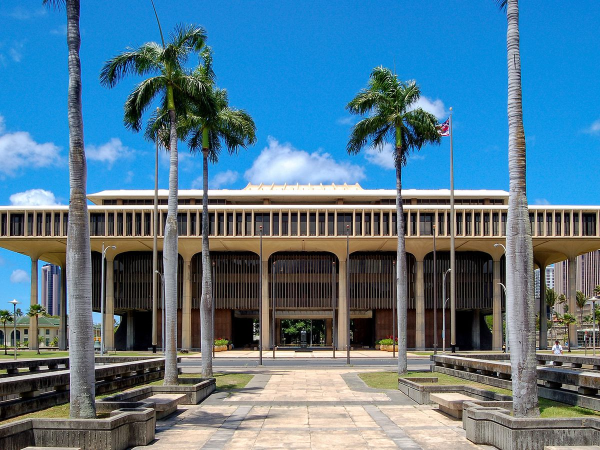 A path lined with palm trees leads to a grand government building with a facade of tall columns.