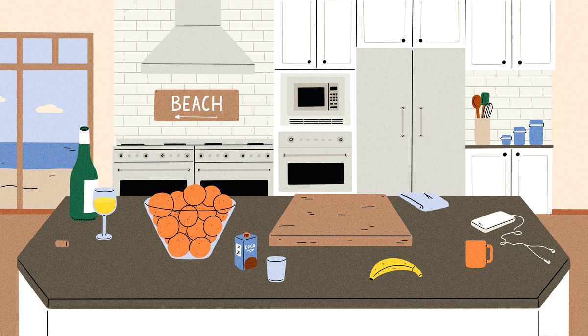 """A bottle and glass of white wine, a large bowl of oranges, a cutting board and other personal artifacts sit atop large granite island in a luxury kitchen. In the background there's a """"Beach"""" sign above a hooded double stove. Illustration."""