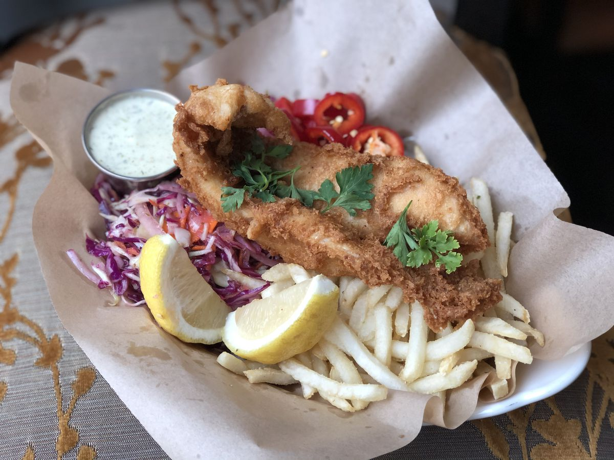 A large piece of fried walleye in a basket with skinny little French fries