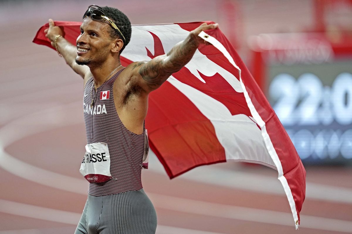 Andre de Grasse celebrates winning the gold medal in a track event during the Tokyo 2020 Olympic Summer Gamesby holding the Canadian flag stretched out behind him.
