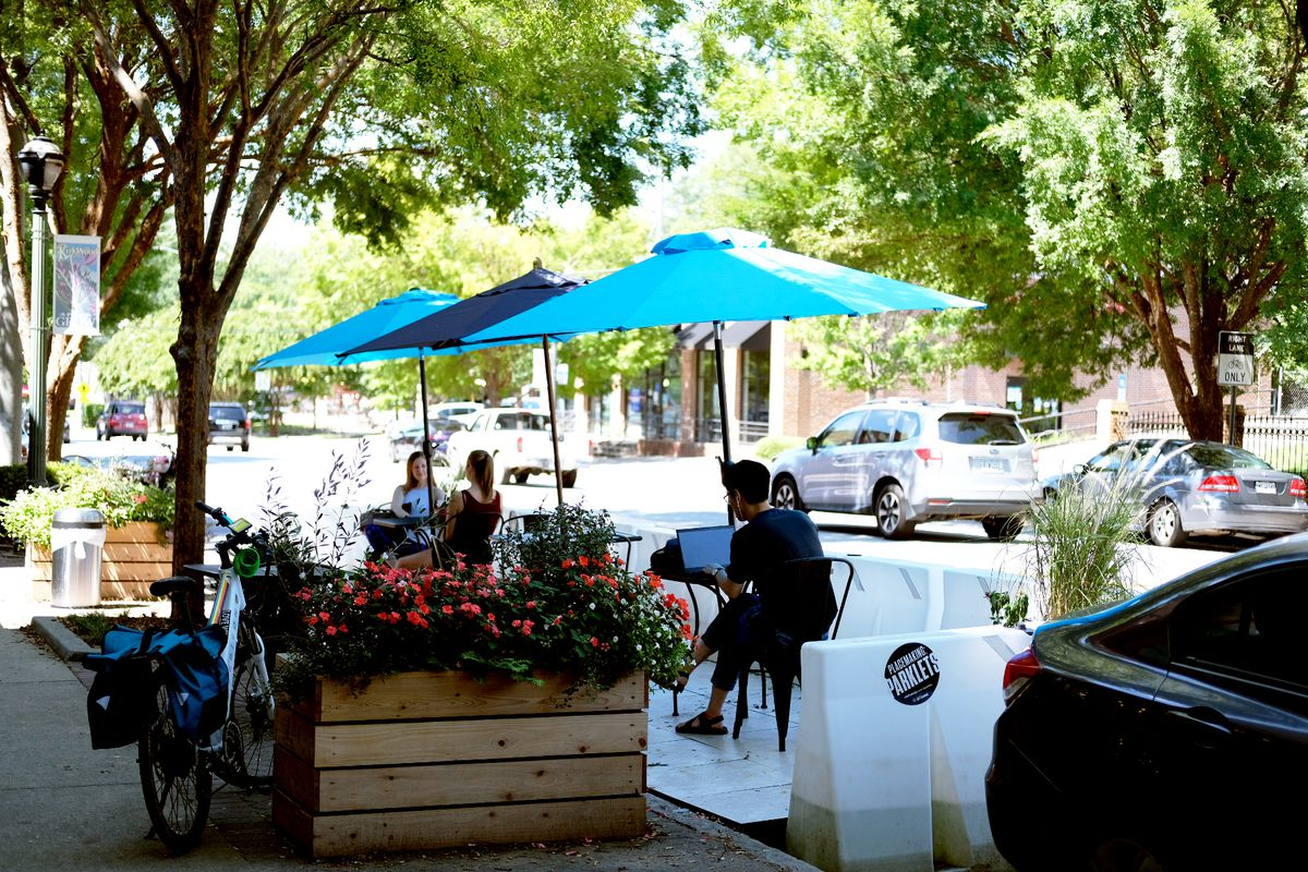 Two women grab coffee at a black metal table under a green umbrella at Taproom Coffee's parklet in Kirkwood Atlanta, while a man in glasses, a black tee shirt, and black pants sits at another table working on his computer on a sunny day.