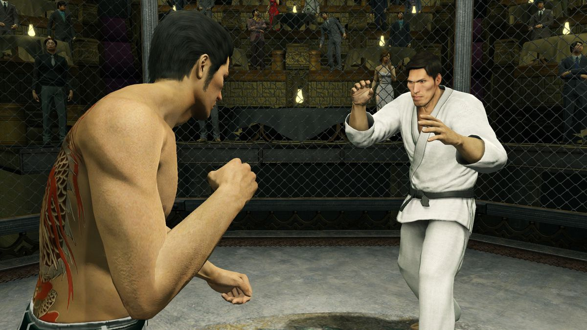 In this screenshot from Yakuza Kiwami, main character Kazuma Kiryu is shirtless, with his large back tattoo of a dragon partially visible as he faces away from the camera. He has his fist up, preparing to fight, and appears to be in a cage with one other
