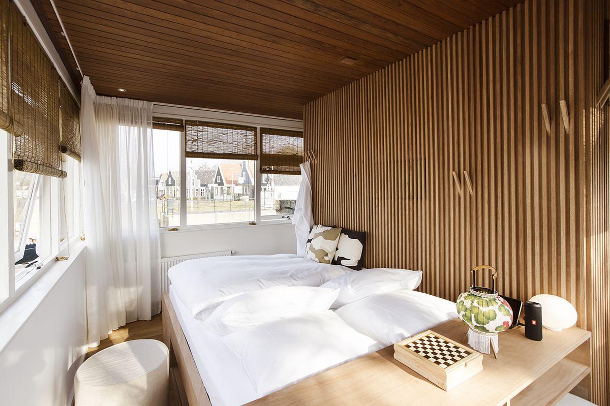 White bed inside light wood hotel room