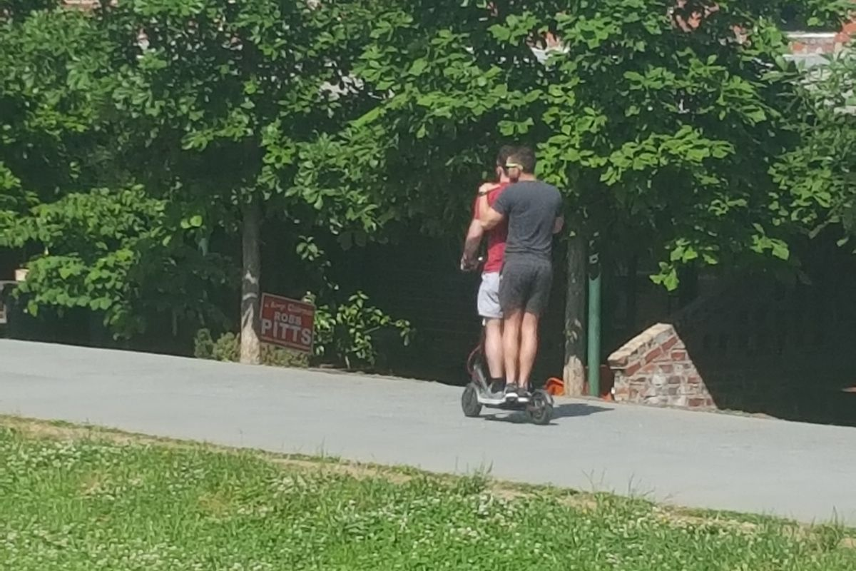 a photo of two people riding one Bird scooter on the Beltline
