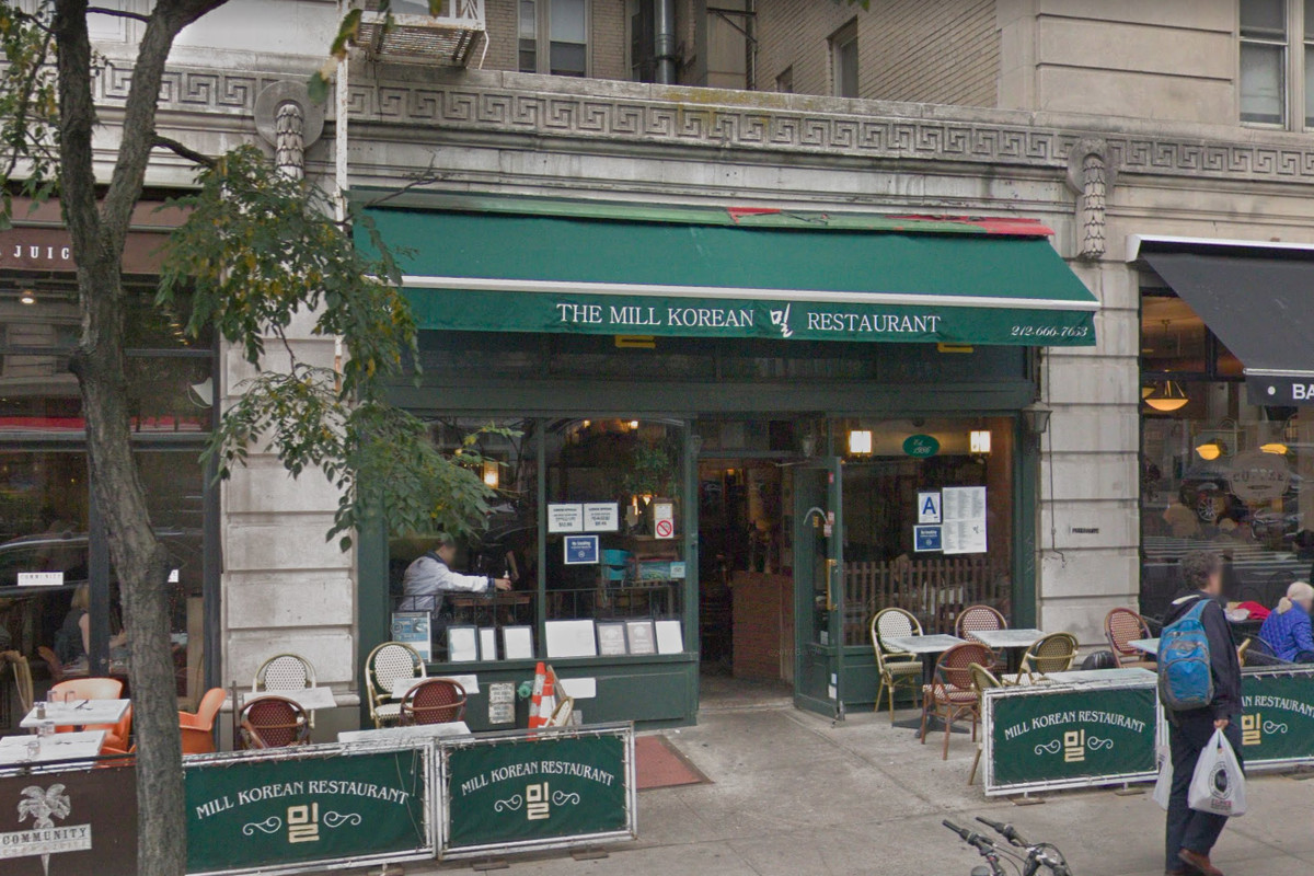 """A restaurant storefront with a green awning emblazoned with """"The Mill."""" Patio seating on the sidewalk is set up with green dividers sectioning off the tables."""