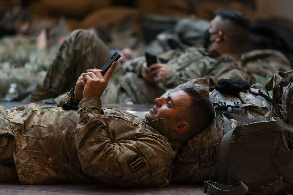 A member of the National Guard taking his break together with his unit at the U.S. Capitol Visitor Center, looks at his phone, Wednesday, Jan. 13, 2021, in Washington.