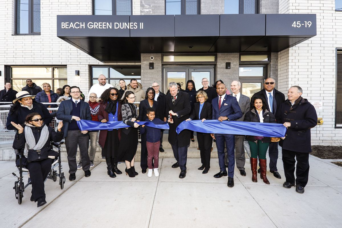 A group of developers and civic leaders stand outside a new apartment building and cut a ribbon to celebrate its opening.