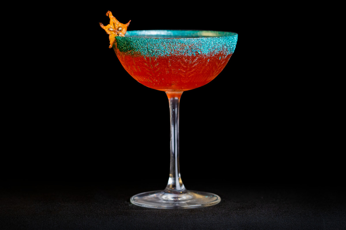 An orange cocktail in a blue glass on a black background