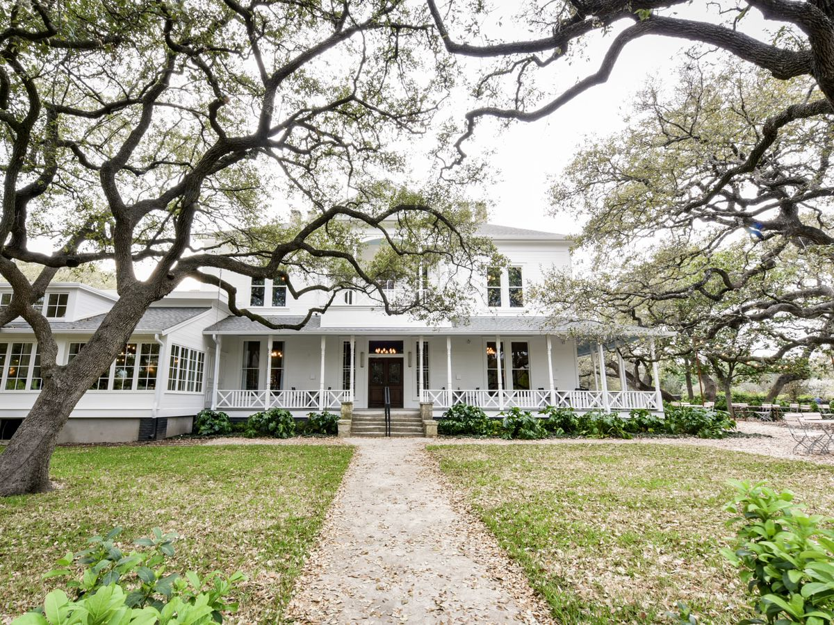 Big frame white wooden 1900s house with big lawn in front