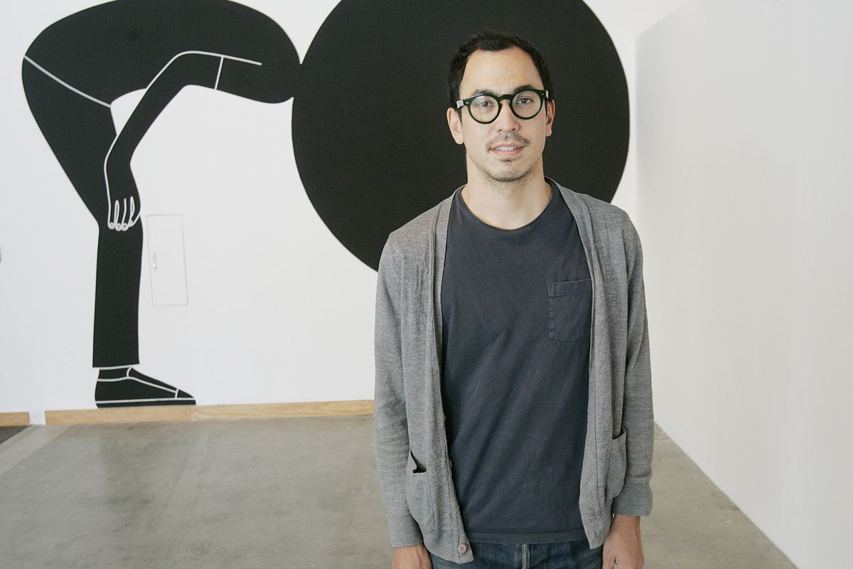 A 2008 photo of Geoff McFetridge standing in front of one of his installations at the RedCat Gallery in Disney Hall.