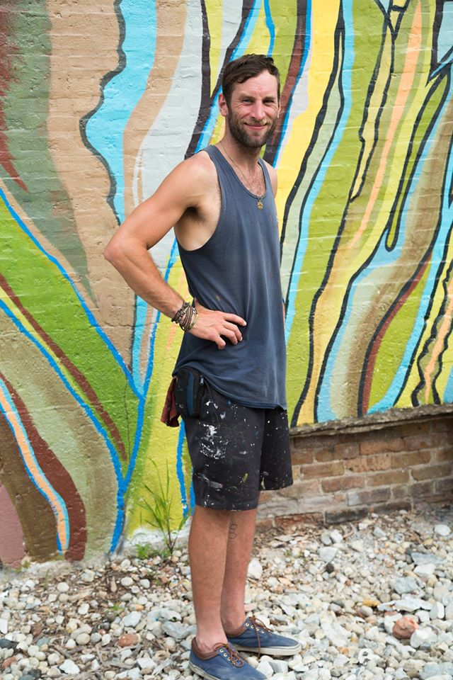 Chicago artist Joe Miller in warmer days at his mural at 1400 W. 46th St.