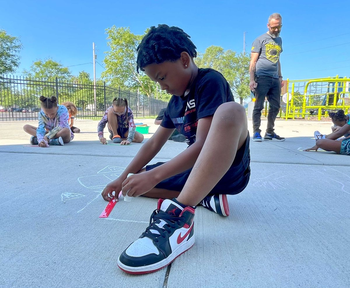 A boy wearing Nike sneakers and black clothing draws on the ground with a piece of chalk, as other children draw on the ground nearby.