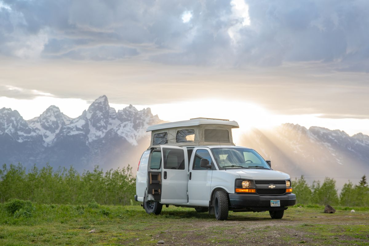 A white Chevy Express camper van with doors open and the top popped open for sleeping. The van sits in a grassy green field in front of Aspens and the snow-covered Teton Mountain Range in the background.