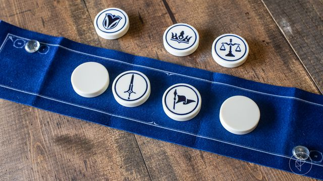 A game of Tellstones laid out on the table. It's played on a blue felt mat with large clay pucks.
