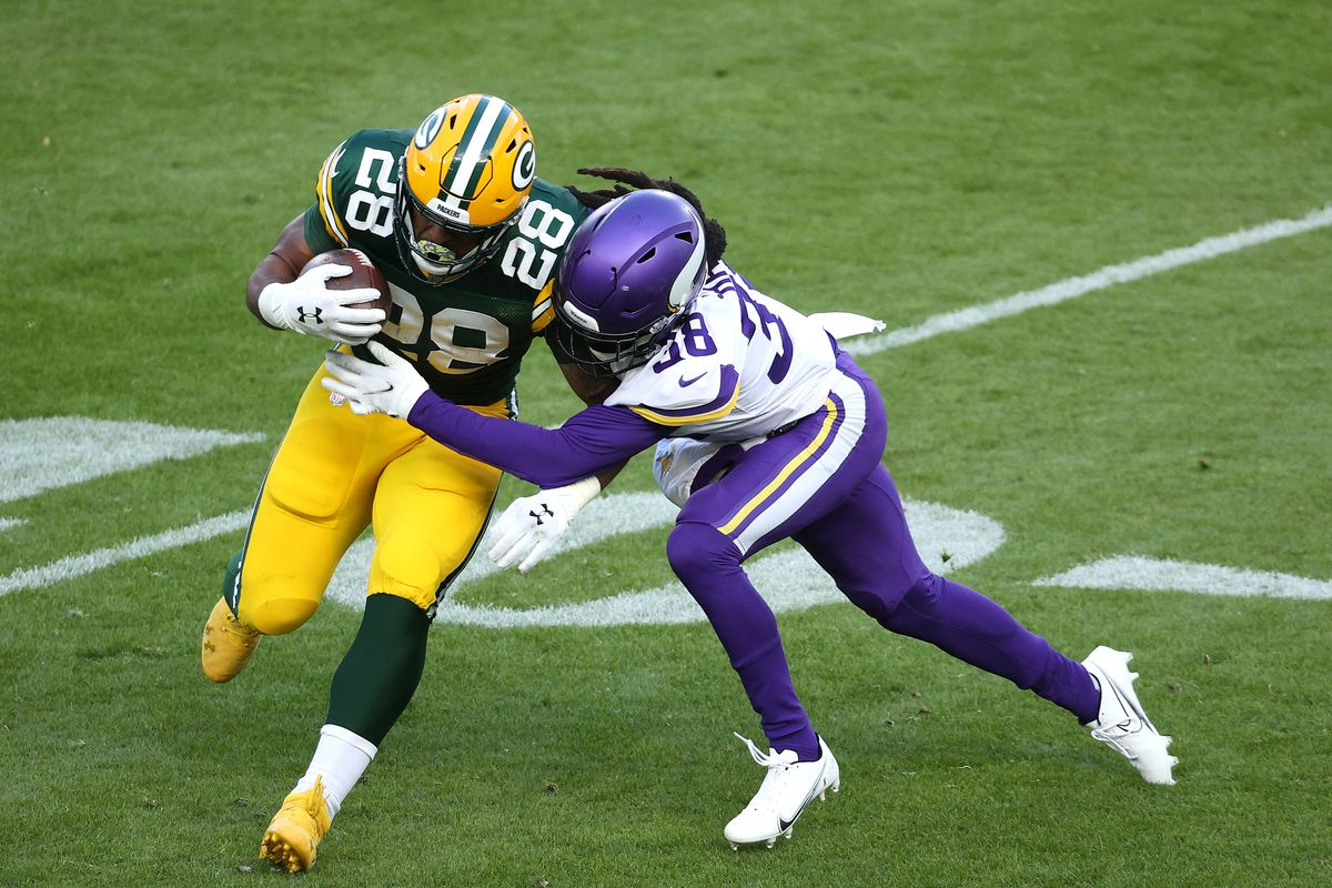 AJ Dillon #28 of the Green Bay Packers runs the ball as Harrison Hand #38 of the Minnesota Vikings tackles during the fourth quarter of the game at Lambeau Field on November 01, 2020 in Green Bay, Wisconsin.