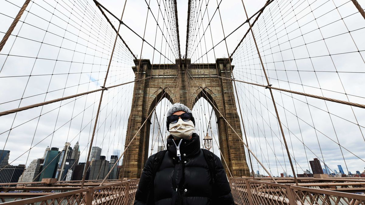 A person wearing a breathing mask standing with the uprights of the Brooklyn Bridge behind them.