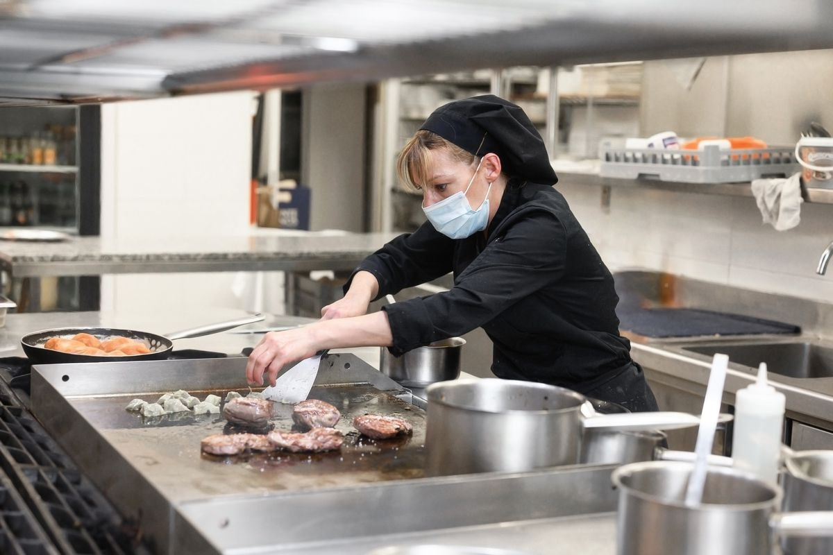 A female chef in a black chef's coat and a surgical mask looks tense as she flips a steak on a griddle in a restaurant kitchen.