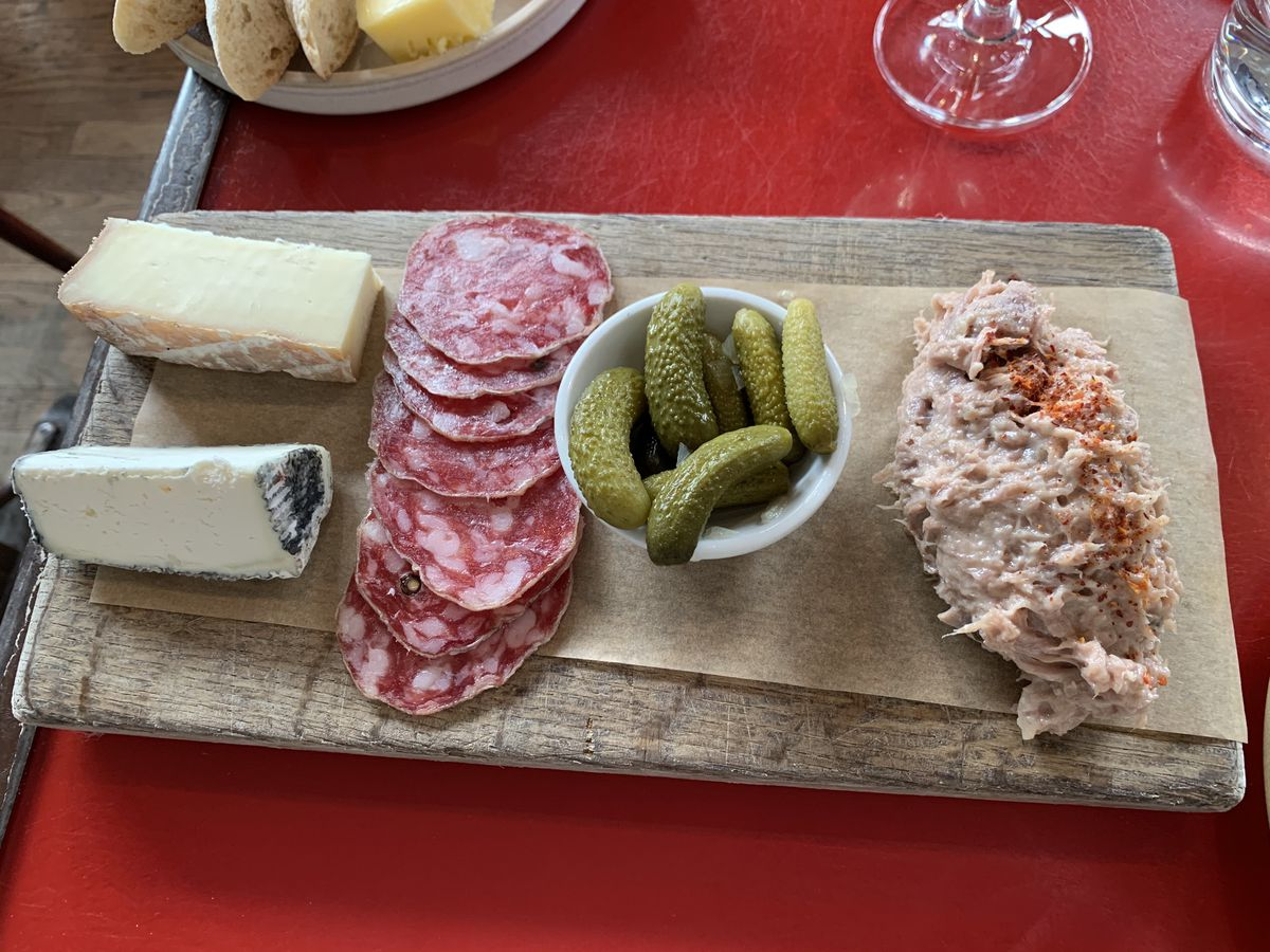 Cheese, salami, and rillettes on a wooden board