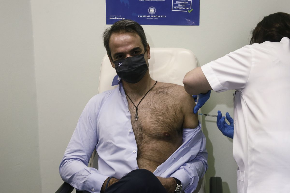 A man wearing a face mask sits in a chair with his shirt unbuttoned and half of his torso exposed as he gets the vaccine.