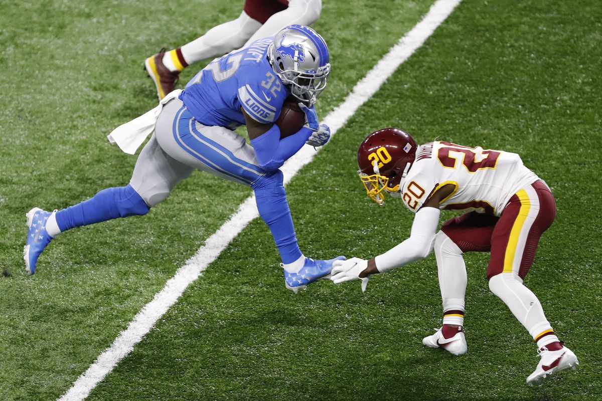 Detroit Lions running back D'Andre Swift (32) runs after a catch for a touchdown during the third quarter against Washington Football Team cornerback Jimmy Moreland (20) at Ford Field.
