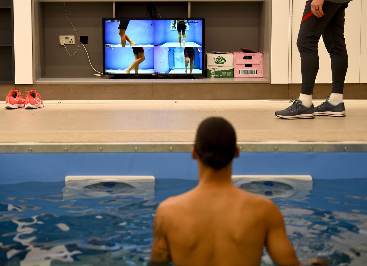 van Dijk watches his movements on screen while immersed in a pool of water at the AXA Training Centre in Kirkby on December 04, 2020. His back is to the camera, and we can see four images from different angles to show how his knee is moving.