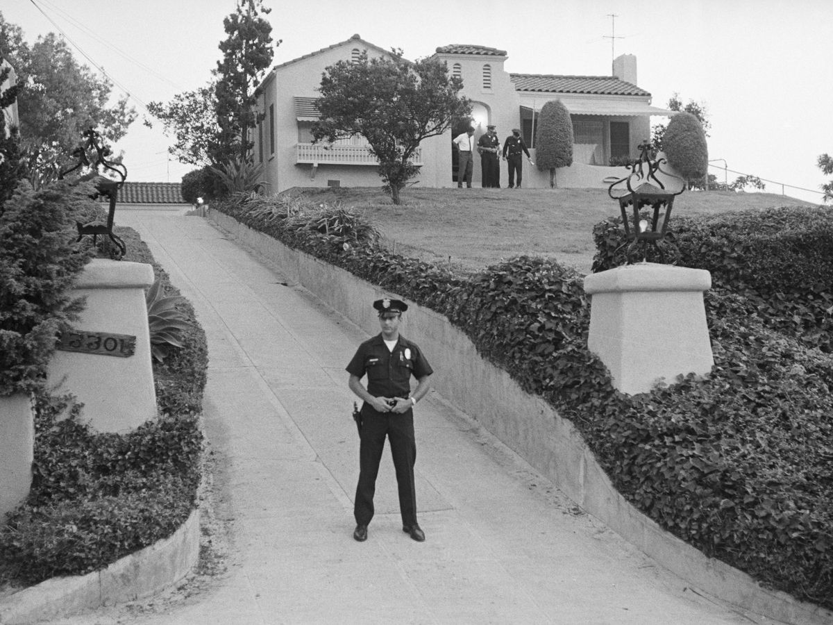 A police officer stands in a driveway that leads up to a house on a hill.