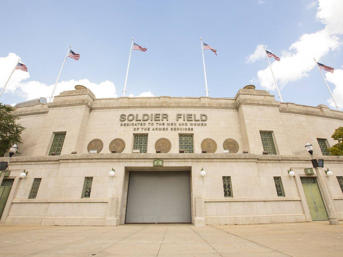 The concrete front facade of Soldier Field stadium, with seven American flag waving.