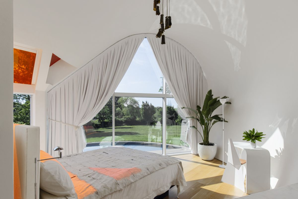 Orange light cast onto bed in bedroom.