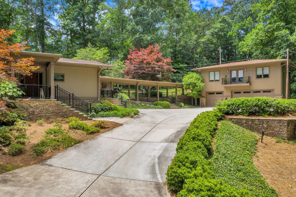 A broad midcentury house with a large garage and long drive.