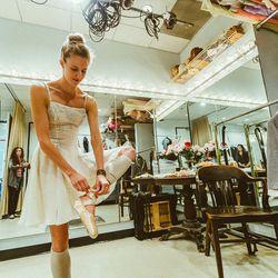A dancer in a Carolina Herrera costume fixes her slipper during her fitting.