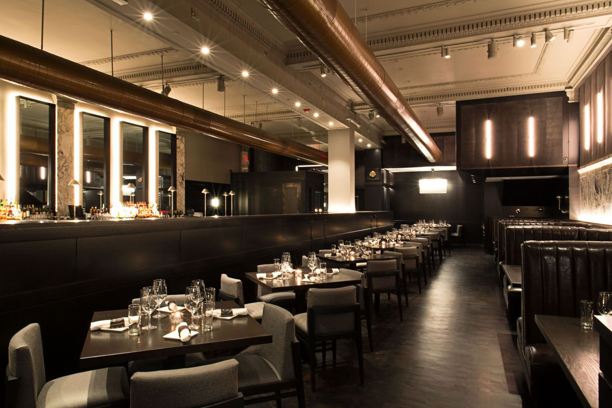 A dark restaurant with wood tables, banquette seating, and place settings