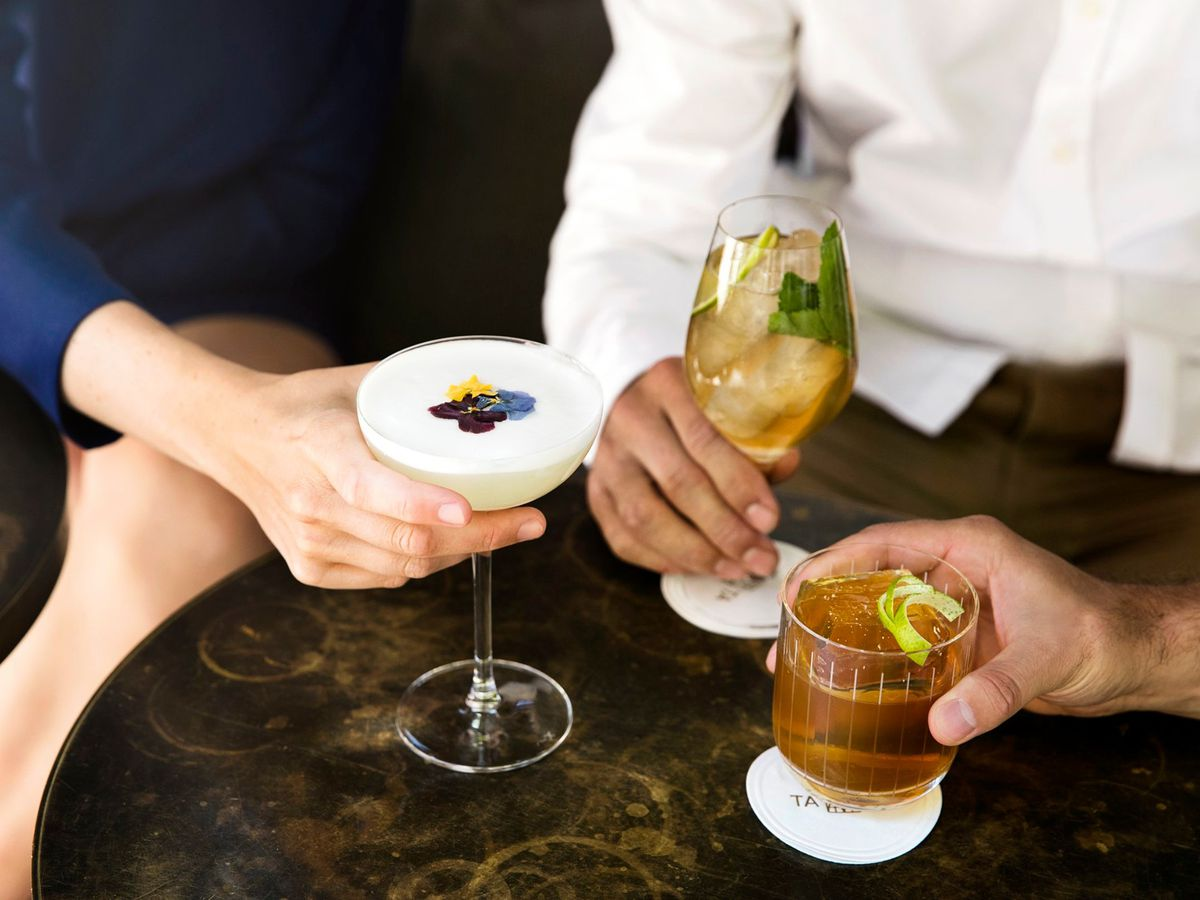 Three people in business casual toast with colorful cocktails in a wine glass, lowball, and coupe