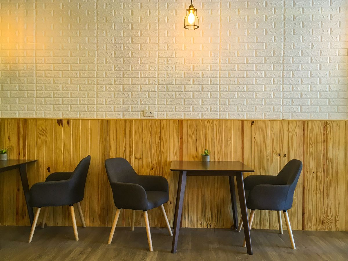 Soft chairs on either side of a table against a wall with wood-grain wainscoting and exposed white brick above. There's another chair and table to the left.