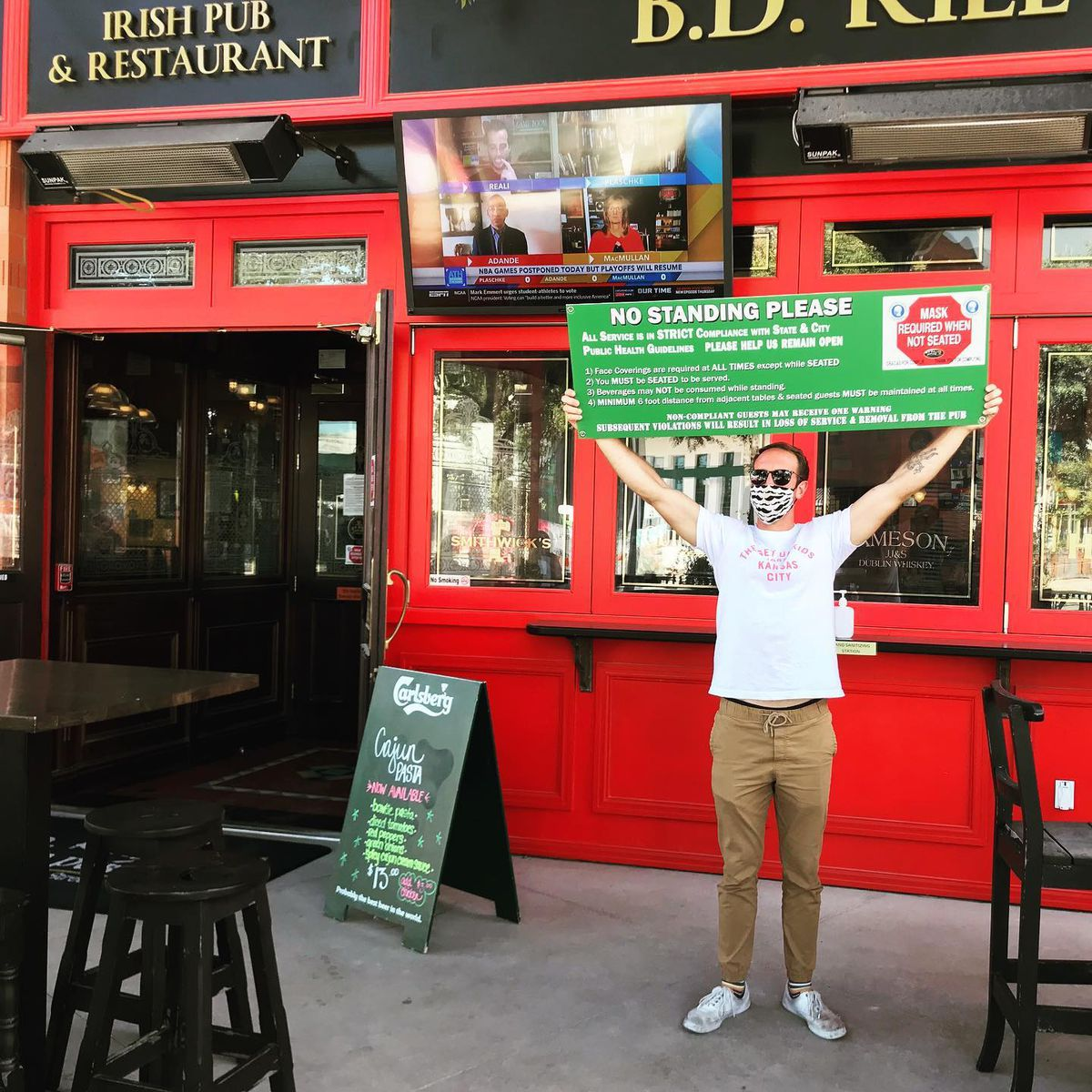 A B.D. Riley's employee holding up the bar's no standing rule signage