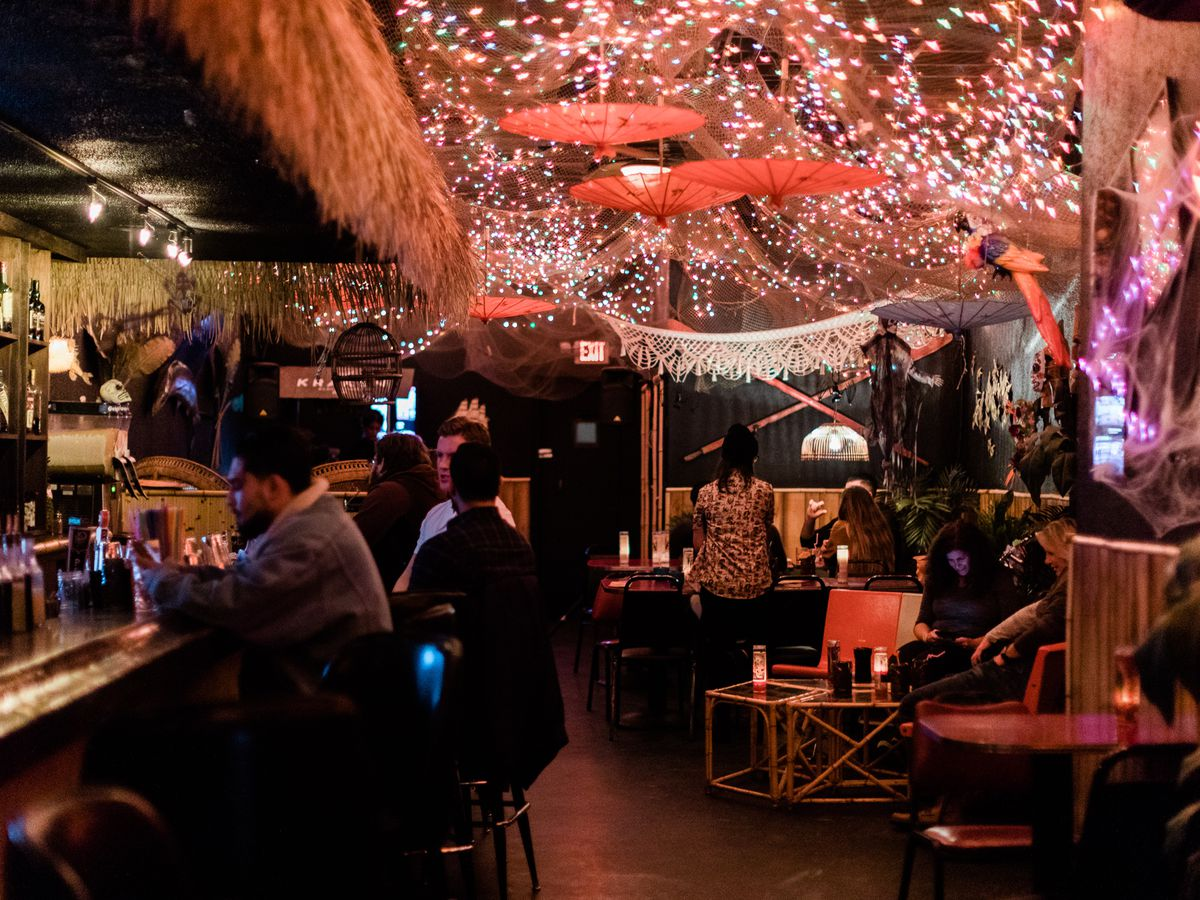 customers sit at the bar inside Mutiny, a tiki bar with netting, lights, paper umbrellas, and a thatched roof over the bar