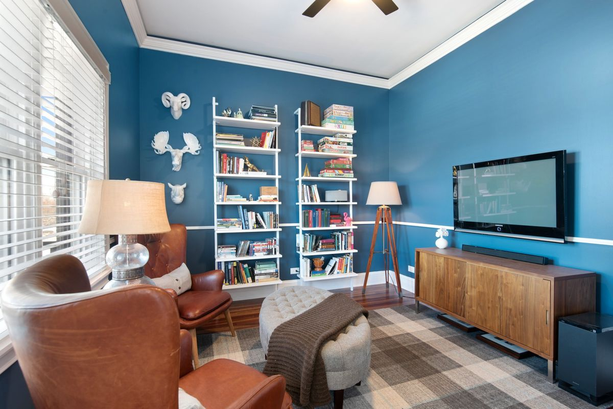 A sitting area with a wall mounted TV, white shelves, and two leather chairs.