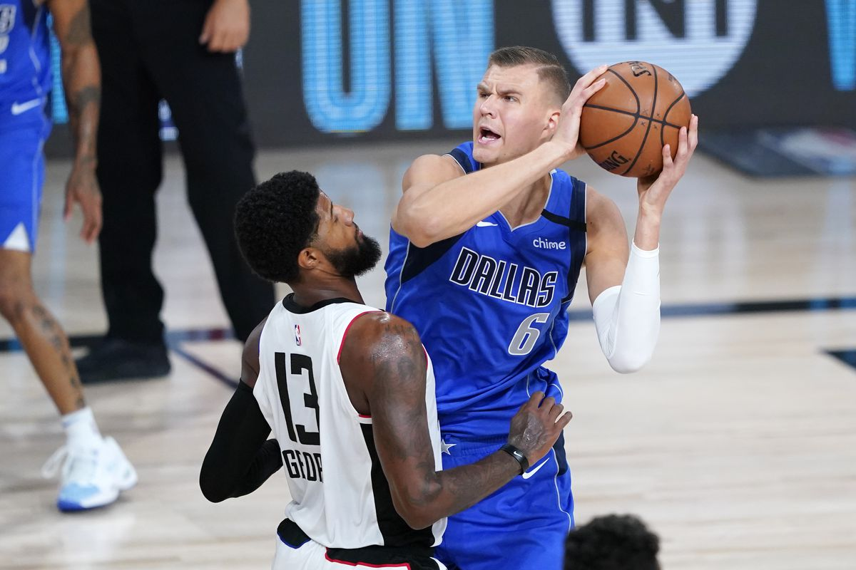 Dallas Mavericks' Kristaps Porzingis is defended by Los Angeles Clippers' Paul George during the second half in a NBA basketball first round playoff game at AdventHealth Arena.