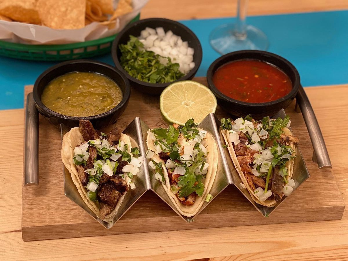 A plate of three tacos with salsas.