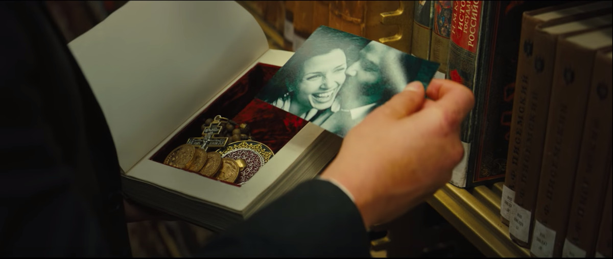 A closeup of John Wick's hand holding a photo of him and his late wife