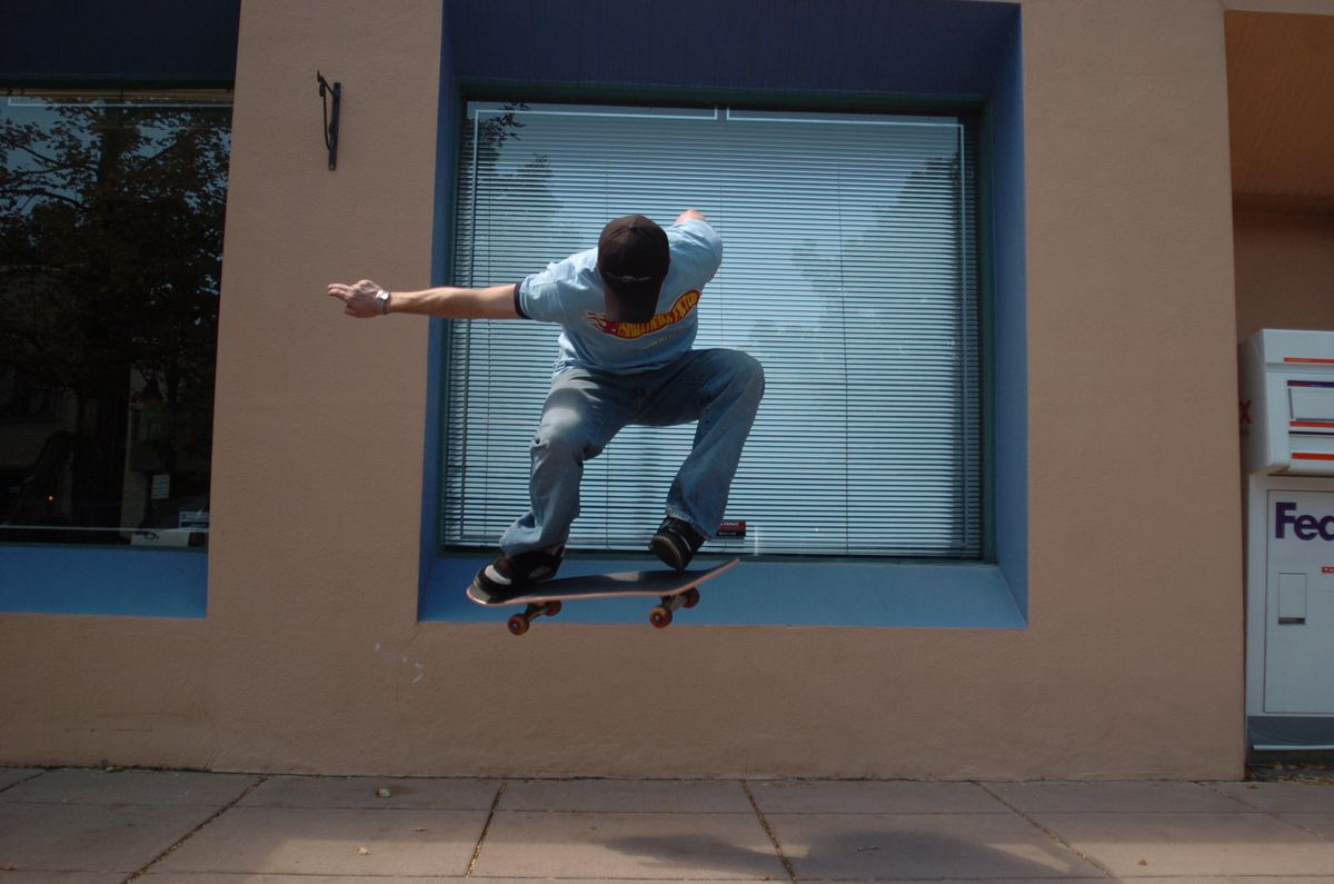 a skateboarder at the peak of his ollie, about to land