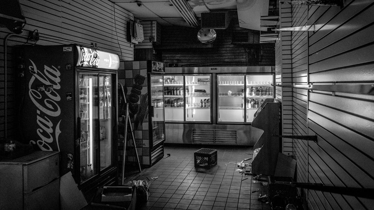 A darkened Gem Spa illuminated by mostly empty drinks coolers