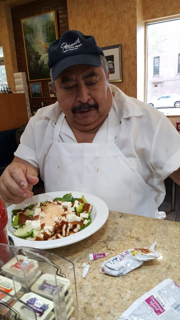 A man in a chef's apron, white shirt, and black hit sits a counter eating lunch