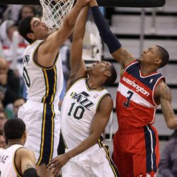 Enes Kanter and Alec Burks, of the Utah Jazz, and the Washington Wizards' Bradley Beal reach for the rebound during a basketball game at the EnergySolutions Arena in Salt Lake City on Saturday, Jan. 25, 2014. The Jazz won 104-101.