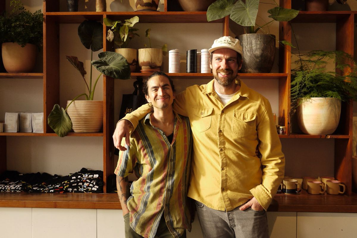 David X. Torres smiles in a striped shirt and John Shaver looks left with his arm around his partner. He wears a yellow shirt and beige hat.