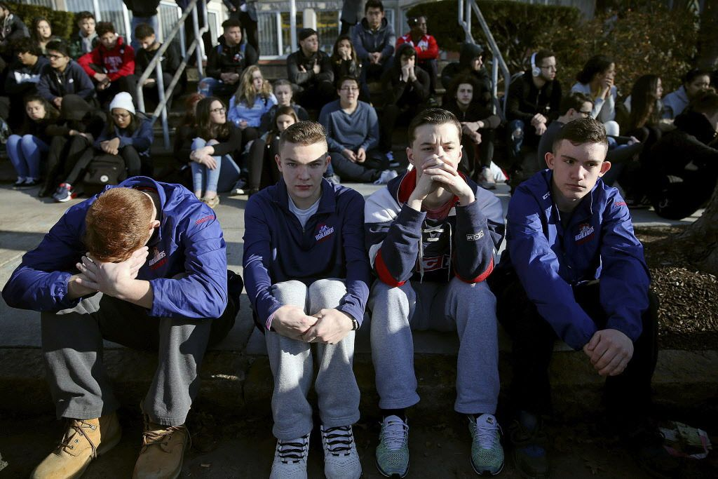 Somerville High School students sit on the sidewalk on Highland Avenue during a student walkout at the school in Somerville, Massachusetts, on Feb. 28, 2018. | Craig F. Walker/The Boston Globe via AP