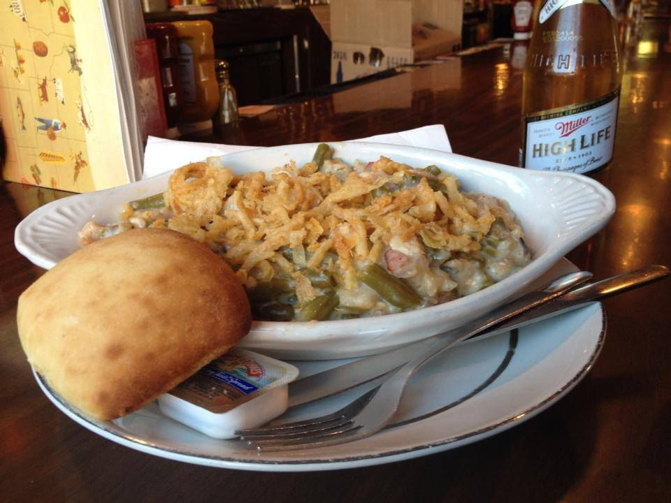 A plate of green bean casserole beneath fried onions on a serving dish with a roll, sitting on a wooden bar with a bottle of High Life
