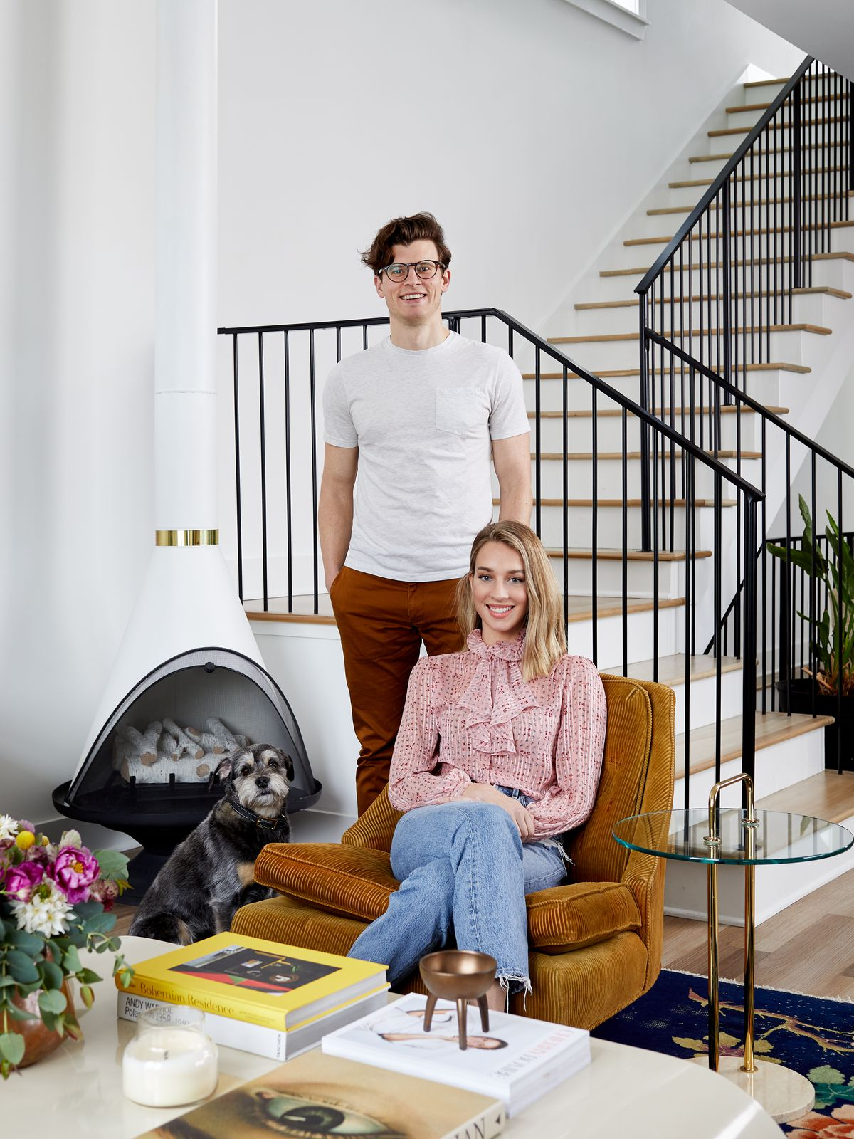The homeowners, a man and a woman in their living room. The woman sits on an orange armchair. The man stands behind her. Behind them is a staircase. There is a dog sitting beside the woman.