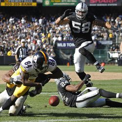 Pittsburgh Steelers wide receiver Antonio Brown (84) fumbles the ball near the goal line while being brought down by Oakland Raiders linebacker Philip Wheeler during the third quarter of an NFL football game in Oakland, Calif., Sunday, Sept. 23, 2012. An unnecessary roughness penalty against the Raiders was called on the play giving the Steelers a touchdown. In the background are Raiders defensive end Dave Tollefson (58) and free safety Michael Huff (24).