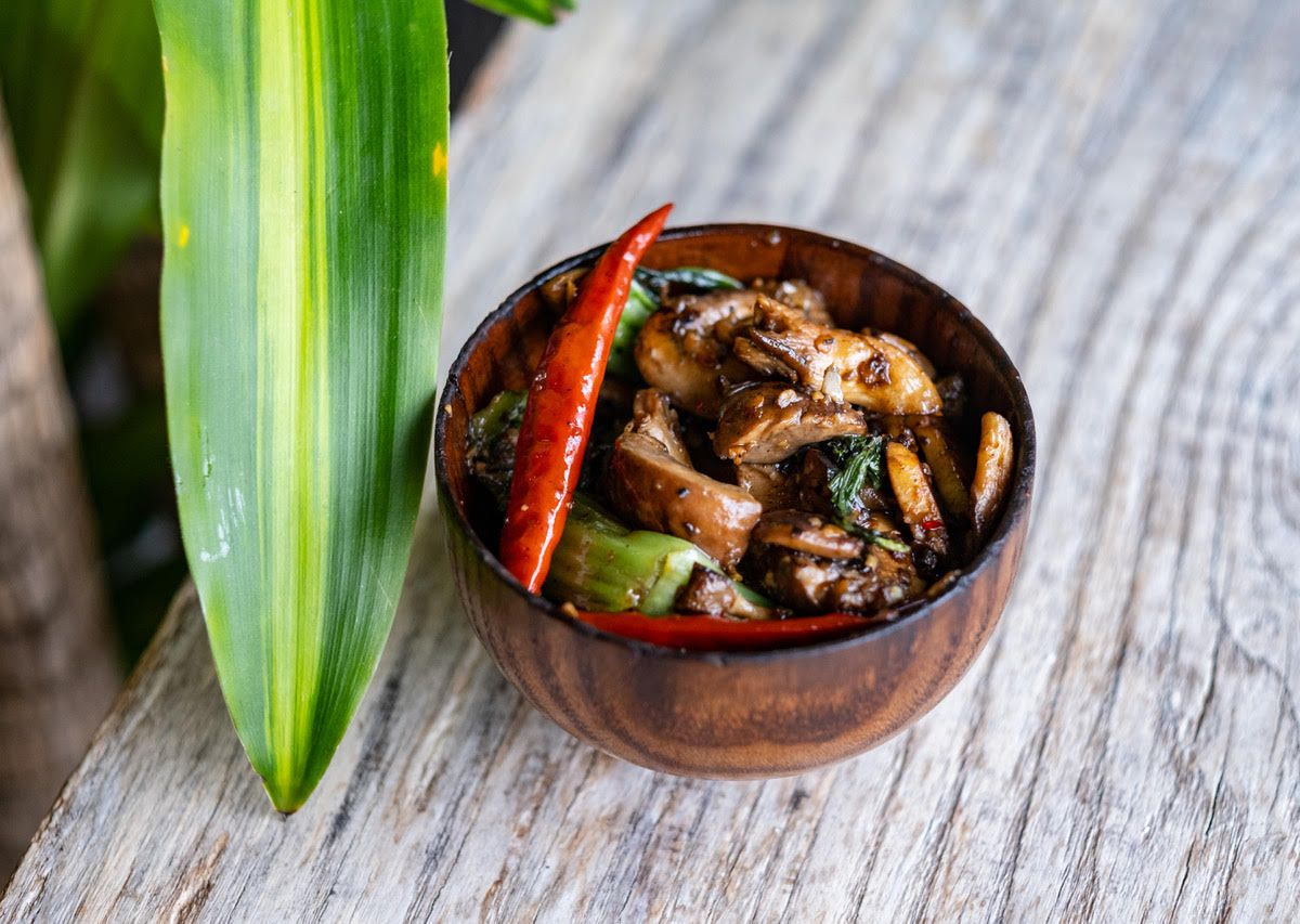 A small wooden bowl of glossy mushrooms, garnished with a skinny red chile pepper. The bowl sits on a light wooden surface.